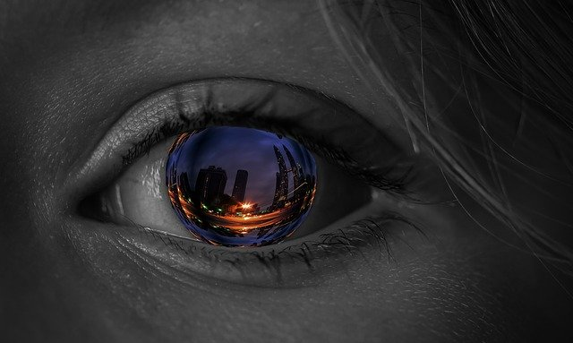 a picture of an eye with an image of a city reflected in it